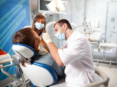 Dentist and assistant cleaning a person's teeth