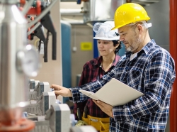 Two engineers check the status of equipment in a manufacturing facility