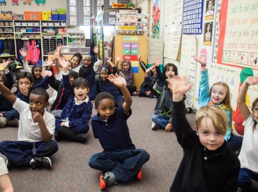 Young students raising their hands in a classroom