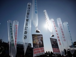 North Korean defectors living in South Korea hold balloons containing leaflets and CDs denouncing Kim Jong-un near the demilitarized zone north of Seoul, February 16, 2013