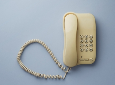 Vintage home telephone over blue background, above view.