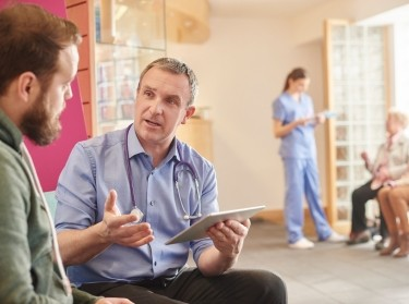 Male doctor with tablet talking to male patient in the waiting room