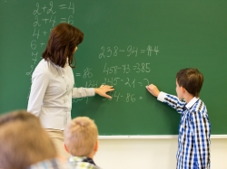 Student with math teacher writing on chalk board