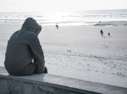Solitary person in a parka sitting on a sea wall