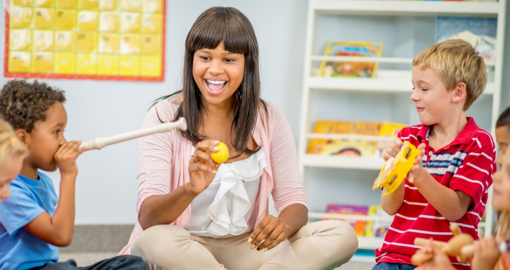A group of preschool children sit with their teacher and play musical instruments