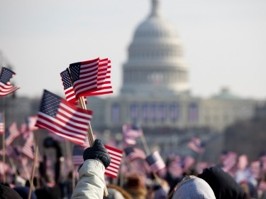 Crowd waving flags in front of the U.S. Capitol during a presidential inauguration