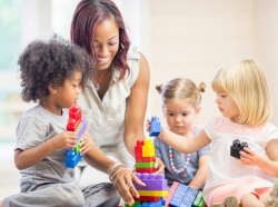 Preschool students and a teacher building a tower with blocks