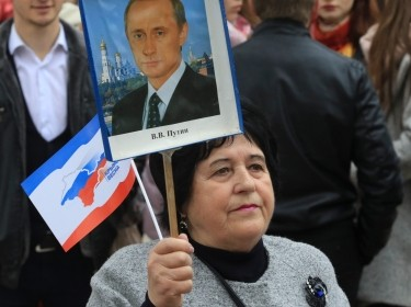 A woman holds a placard with a portrait of Russian President Vladimir Putin during a celebration of the third anniversary of Russia's annexation of Crimea in Simferopol, March 16, 2017