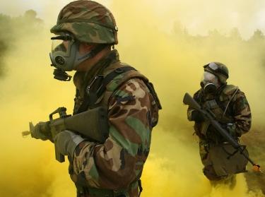 Sailors patrol through yellow smoke simulating chemical, biological, and radiological exposure during combat