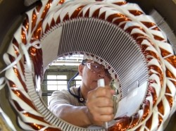 An electrician mechanic rewinds a stator at Puget Sound Naval Shipyard and Intermediate Maintenance Facility