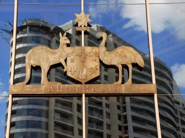 The Australian Coat of Arms in metal hangs on the glass wall of a building