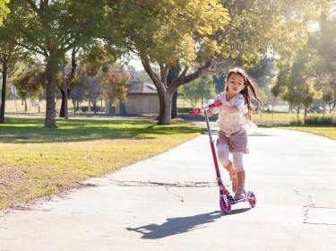 Little girl riding a scooter in a park