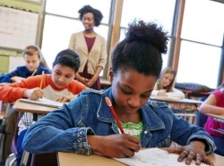 A student in an elementary classroom drawing in her notebook