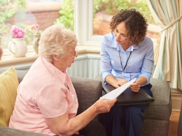 Home health worker speaking with elderly woman in her home