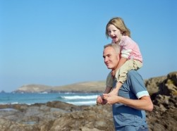 Father carrying daughter on his shoulders by the sea in Cornwall, England