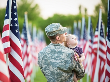 American soldier with daughter, surrounded by American flags