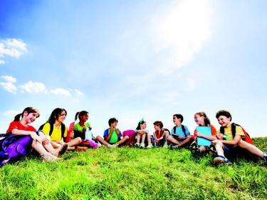 Children wearing school backpacks sit outdoors on grass