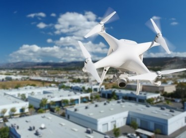Unmanned aircraft system (uav) quadcopter drone in the air over commercial buildings