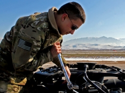 Crew Chief Pfc. James Dennis performs a torque check on the main rotor head of a UH-60 Black Hawk helicopter