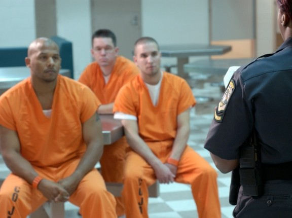 Three inmates listening to a prison guard