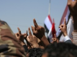 Anti-government protesters outside Sana'a University raise their fingers and fists in the air while chanting for a new Yemen, February 25, 2011