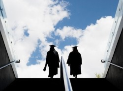 Two students in their graduation robes walking up steps