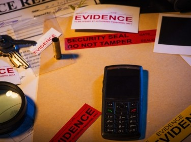 Police desk with crime case records containing a mobile phone, photos, and keys