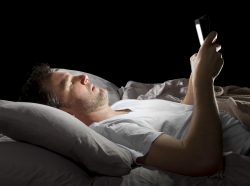 Man in bed looking at a tablet