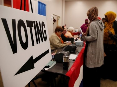 Voters stand near a voting sign before casting ballots during early voting