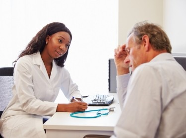 Female doctor in her office consulting with a male patient