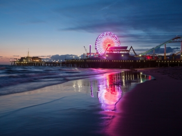 The Santa Monica Pier in California, illuminated at night with a reflection on shoreline