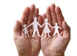 hands holding paper cutout of family