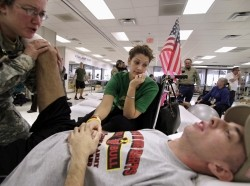 Sgt. John Kriesel receives treatment from a therapist while his wife, Katie, comforts him at the Walter Reed Army Medical Center in Washington, February 9, 2007