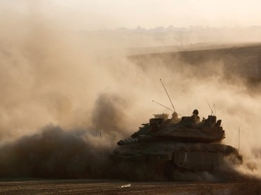 An Israeli tank drives near the border as it returns to Israel from Gaza August 3, 2014