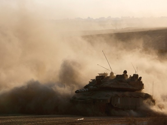 An Israeli tank drives near the border as it returns to Israel from Gaza, August 3, 2014