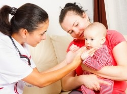 A medical professional visiting an infant and her mother at home