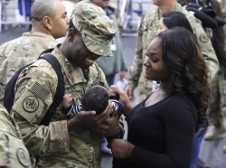 U.S. Army officer returning from Afghanistan holds his son for the first time during a redeployment ceremony at Fort Hood, December 9, 2016