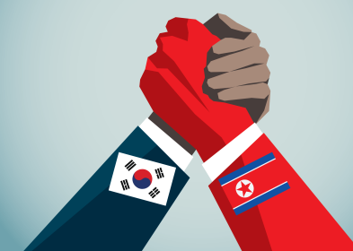 Hands with South Korean and North Korean flags clasp one another