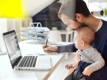 Dad works from home, holding baby on his lap