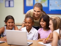 A teacher and four students looking at a laptop