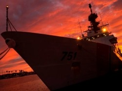 A Coast Guard ship tied up at sunset
