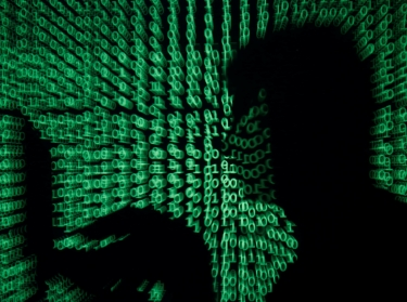 A man holds a laptop computer as cyber code is projected on him