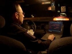 A male police officer working on a laptop while sitting in a vehicle