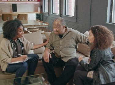 African American female staff member talks with an older couple
