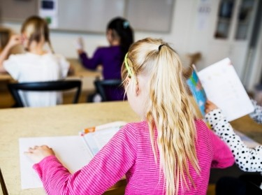 A child seen from behind sitting at a classroom desk reading