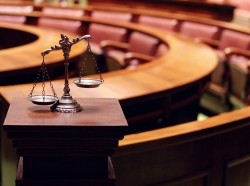 A scales of justice in a courtroom with jury seats in the background