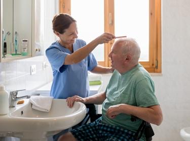 Female caregiver combing an elderly man's hair in the bathroom
