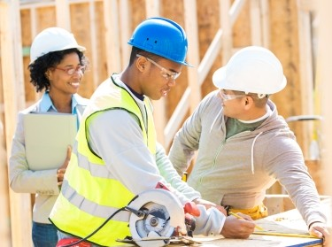 A woman and two men in hard hats on a construction site