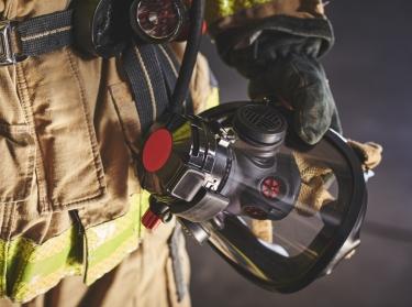 A firefighter holding an oxygen mask