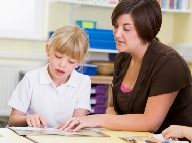 Elementary student reading with her teacher